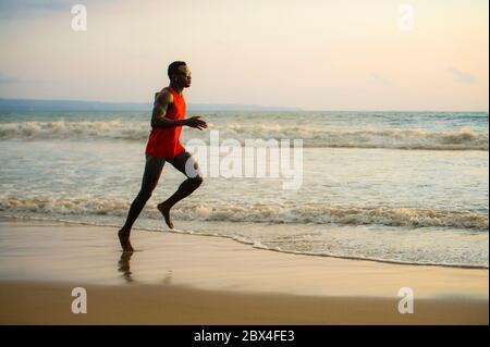 Jeune coupe attrayante athlétique et fort noir Africain américain homme courant à la plage entraînement dur et sprint sur l'eau de mer dans professionnel athl