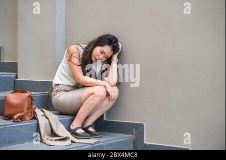 Jeune femme d'affaires asiatique japonaise en dépression et désespérée pleurant seule assis sur un escalier de rue souffrant de stress et de dépression crise d'être vict Banque D'Images