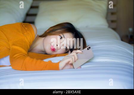 Jeune fille asiatique coréenne attrayante et détendue utilisant un téléphone mobile à la chambre à la maison appréciant Internet en ligne datant application ou les médias sociaux couché sur le lit Banque D'Images