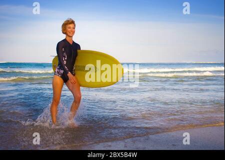 jeune fille blonde belle et attrayante surfeuse sur la plage avec planche à voile jaune marchant hors de l'eau en profitant des vacances d'été à tropi Banque D'Images