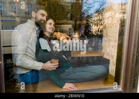 Jeune couple, assis dans un café et regardant la fenêtre, se embrassant, manger des croissants frais. Drôle petit garçon fils montrant des gestes et Banque D'Images