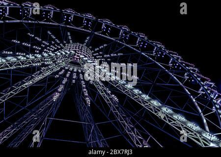 Vue de l'angle de la roue des ferris lumineux au néon bleu sur fond noir. Banque D'Images