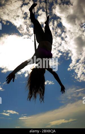 aero yoga beach entraînement - silhouette de jeune femme attrayante et athlétique pratiquant l'entraînement aérien yoga entraînement acrobatique corps postures sur bleu
