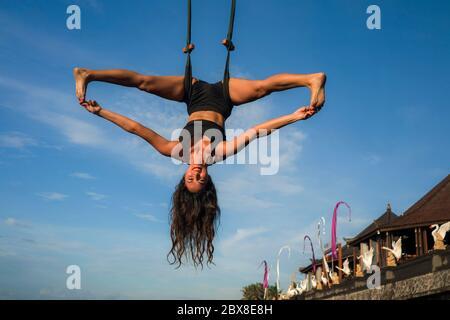 entraînement aero yoga - jeune femme attrayante et athlétique pratiquant l'entraînement aérien yoga entraînement acrobatique corps postures isolées sur le ciel bleu à bala
