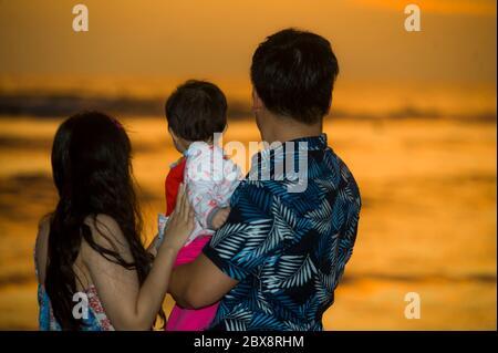 silhouette de jeune heureux et beau couple tenant bébé fille appréciant coucher de soleil plage ensemble regardant la mer dans les vacances romantiques famil Banque D'Images