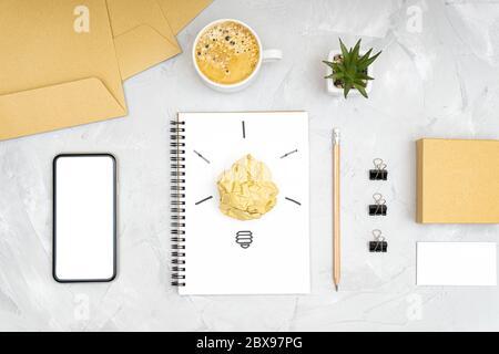 Concept de pause de rafraîchissement et de stimulation de la productivité. Plan d'un bureau avec un smartphone, une tasse à café, un symbole d'ampoule en cron Banque D'Images