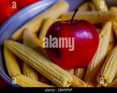 Cornes fraîches de pommes et de bébés disposées dans un panier avec tomates et légumes verts en arrière-plan Banque D'Images