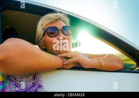 Portrait de style de vie de femme asiatique indonésienne d'âge moyen, attrayante et heureuse, 40 ou 50, avec des cheveux gris et un beau sourire assis dans sa voiture enjoyi