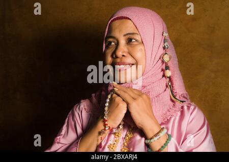 Portrait isolé en studio d'une femme musulmane âgée heureuse et positive dans ses années 50 portant un foulard hijab traditionnel de l'Islam priant en tenant des perles de prière