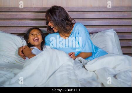 Portrait de la chambre de style de vie de la femme asiatique heureuse à la maison jouant avec la petite fille dans le lit cuddling et rire gai dans la mère et l'enfant amour an