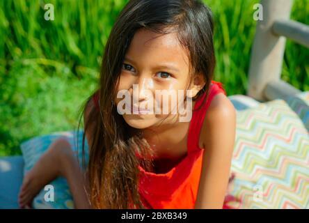 portrait de style de vie extérieur de belle et douce jeune fille souriant heureux et gai l'enfant avec les yeux magnifiques et vêtu d'une robe rouge isola