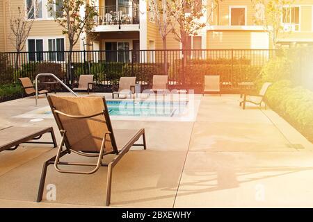 Piscine résidentielle avec chaises longues et chaises longues vides dans un complexe d'appartements moderne Banque D'Images