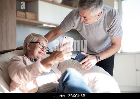 un couple de personnes âgées heureux parlant via la liaison vidéo dans leur salon. Banque D'Images