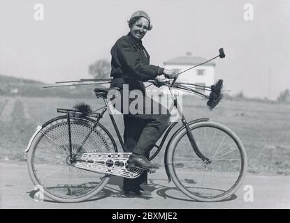 Balai de cheminée. Une femme qui travaillait comme balayeuse de cheminée n'était pas une vue commune à ce moment-là dans les années 1940. Elle utilise sa bicyclette pour se transporter elle-même et son équipement de maison en maison. Suède 1940 Banque D'Images