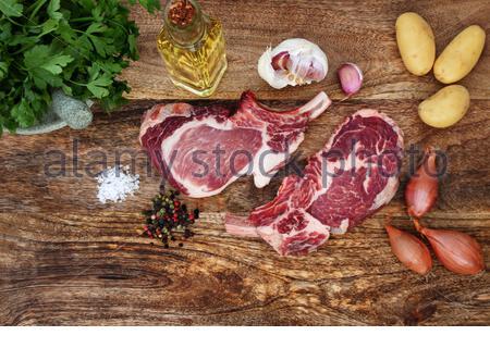 Boeuf cru avec des épices et ingrédients pour la cuisson sur une planche en bois rustique Banque D'Images