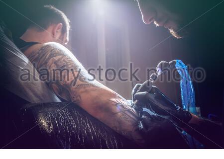Portrait d'un homme maître de tatouage montrant un processus de création de tatouage dans une main d'homme sous la lampe Banque D'Images