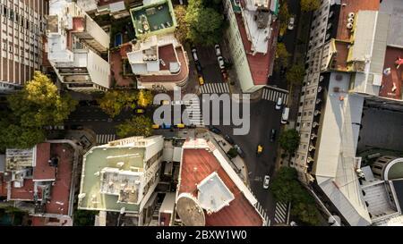 Vue aérienne des bâtiments résidentiels avec la rue principale, arbres d'automne, voitures colorées passant par, différents toits. Banque D'Images