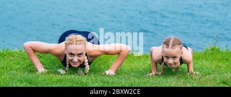 Peu de girt et la femme font des exercices sur l'herbe sur le rivage du lac. Banque D'Images