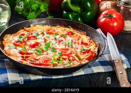 Frittata fait d'oeufs, saucisse chorizo, poivron rouge, poivron vert, tomates, fromage et piment dans une poêle sur table en bois. Cuisine italienne Banque D'Images