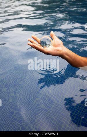Main humaine tenant une boule de verre au-dessus de l'eau Banque D'Images