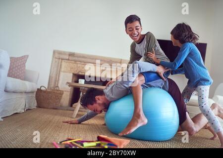 Bonne famille jouant sur le ballon de fitness dans le salon Banque D'Images