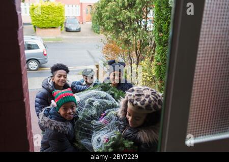 Une famille heureuse apporte un arbre de Noël à la porte d'entrée de la maison Banque D'Images