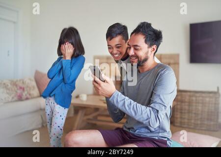 Père et enfants utilisant un smartphone dans le salon