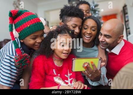 Bonne famille avec un smartphone pour fêter Noël Banque D'Images