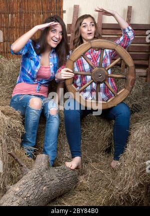 Deux belles filles dans le foin avec une roue sur le wagon Banque D'Images