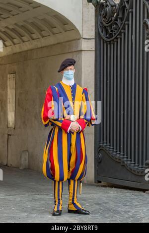 Garde suisse papale en uniforme avec masque médical protecteur au St. La place Pierre au Vatican pendant la pandémie de Covid 19 Banque D'Images