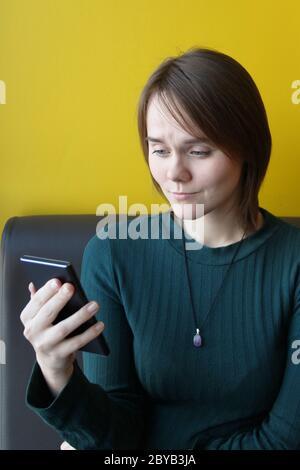 Une jeune fille d'apparence européenne dans une veste bleue est assise dans un café avec un téléphone mobile sur le canapé sur fond de mur jaune. Place pour le texte, espace de copie. Banque D'Images