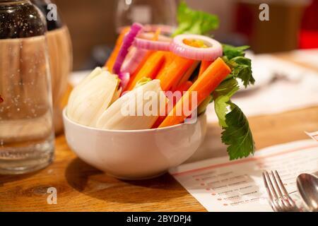 Bol de bouddha vegan. Bol de légumes frais crus - radis, carottes, ognion, radis, persil vert dans une assiette en céramique blanche sur une table en bois. Hôtel br Banque D'Images