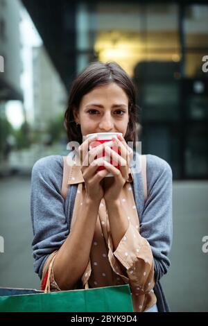 Une jeune femme heureuse à boire du café et à marcher avec des sacs après avoir fait du shopping en ville.