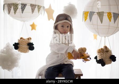 Mignon petit enfant, garçon, jouant avec des poussins à la maison, prétendant qu'il vole dans le ciel, pilote avec avion et poussin d'animal de compagnie