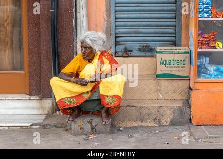 Chennai, Tamil Nadu, Inde - août 2018 : une femme indienne âgée portant un sari rouge et jaune coloré assis sur le trottoir. Banque D'Images