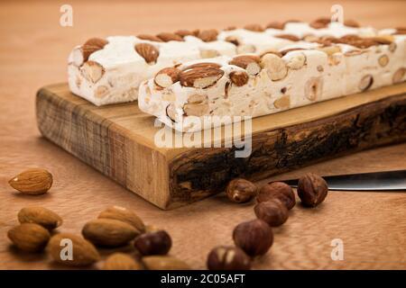 Blocs de Turron avec amandes et noisettes sur planche à découper, sur table en bois, gros plan