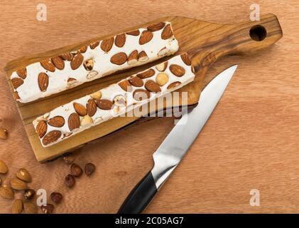 Blocs de turron doux aux amandes et noisettes sur planche à découper, avec couteau sur table en bois, vue en grand angle
