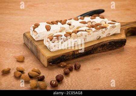 Blocs de turron doux aux amandes et noisettes sur planche à découper, avec couteau sur table en bois.