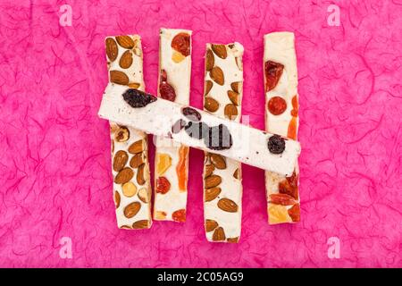 Variété de blocs de tourron avec des noisettes, des amandes, des baies séchées et des fruits confits sur fond rose, vue en grand angle