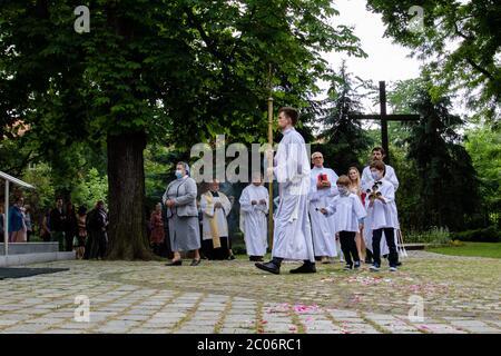 Un serveur d'autel tenant une énorme croix à la paroisse de la Sainte Vierge Marie de Czestochowa à la rue Kochanowskiego pendant la procession.la Fête du corps et du sang du Christ (Corpus Christi) Est une fête dédiée à la vénération du corps et du sang du Christ, dans laquelle le pain et le vin sont transformés pendant l'Eucharistie selon la foi chrétienne. Selon la tradition, une procession solennelle est organisée dans les rues de l'Église catholique ce jour-là. En Pologne, ce jour est un jour férié. Cette année, de nombreux participants au cortège portaient des masques médicaux, dont alt Banque D'Images