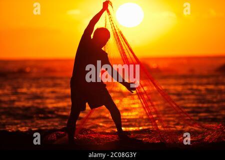 Hawaiian Fisherman (modèle relâché) transporte dans son filet de pêche au coucher du soleil à Keauhou, Hawaï Banque D'Images