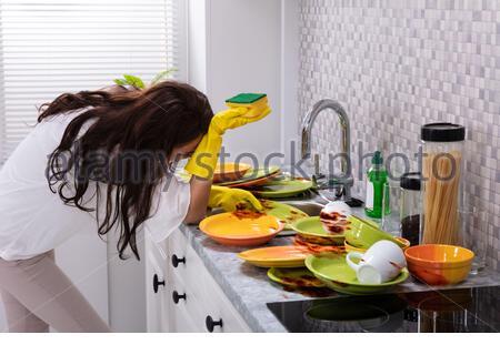 Vue de côté assez jeune femme se penchant près de l'évier avec des ustensiles sales dans la cuisine Banque D'Images