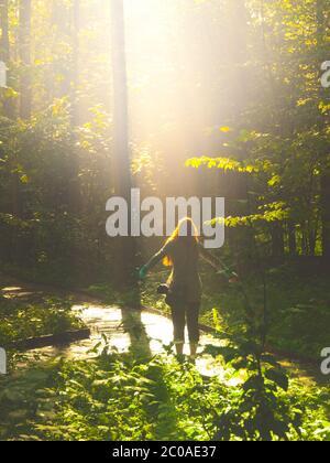 Femme fidèle remerciant dieu avec des bras ouverts dans la nature illuminée par la lumière brillante du ciel. Notion de prière et de foi. Banque D'Images