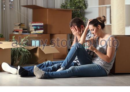 Expulsées triste couple moving home plaint assis sur le plancher dans la nuit Banque D'Images