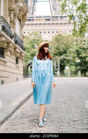 Jolie femme touriste, portant un chapeau élégant et une robe bleue, marchant dans la rue confortable avec les anciens bâtiments d'époque dans la vieille ville européenne de Paris, avec