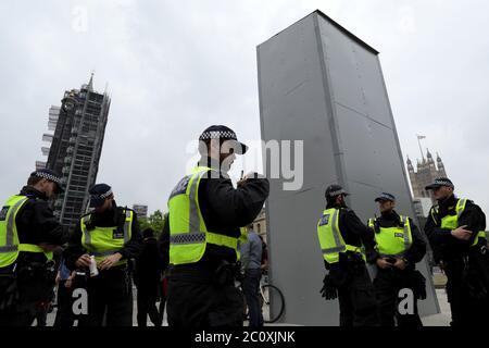 (200612) -- LONDRES, le 12 juin 2020 (Xinhua) -- les policiers se tiennent près d'une boîte de protection installée autour de la statue de Winston Churchill lors d'une manifestation à Londres, en Grande-Bretagne, le 12 juin 2020. Les statues et monuments clés de Londres, dont le Cenotaph à Whitehall, les statues de Winston Churchill et Nelson Mandela, doivent être couverts et protégés avant les manifestations prévues de la Black Lives Matter Matter Weekend, a déclaré le maire Sadiq Khan vendredi. Les manifestations à Londres et dans d'autres villes britanniques ont commencé après la mort de l'Afro-américain sans armes George Floyd le 25 mai à Minneapolis, aux États-Unis Banque D'Images