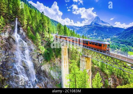 Zermatt, Suisse. Train touristique Gornergrat avec cascade, pont et Cervin. Région du Valais. Banque D'Images