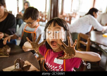 Petite fille asiatique ouvre sa bouche tout en montrant ses mains sales jouant de l'argile avec ses amis