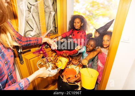 Beaucoup d'enfants divers les garçons et les filles en costumes d'Halloween sont dans la porte avec des seaux orange pour bonbons reçoivent des bonbons d'adulte Banque D'Images