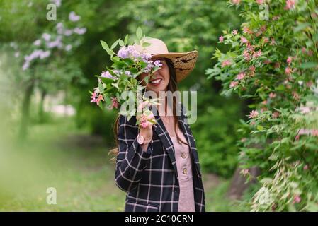 Fille en paille chapeau d'été, robe rose et veste sombre cacher son visage avec un bouquet sur un fond d'arbres en fleur Banque D'Images